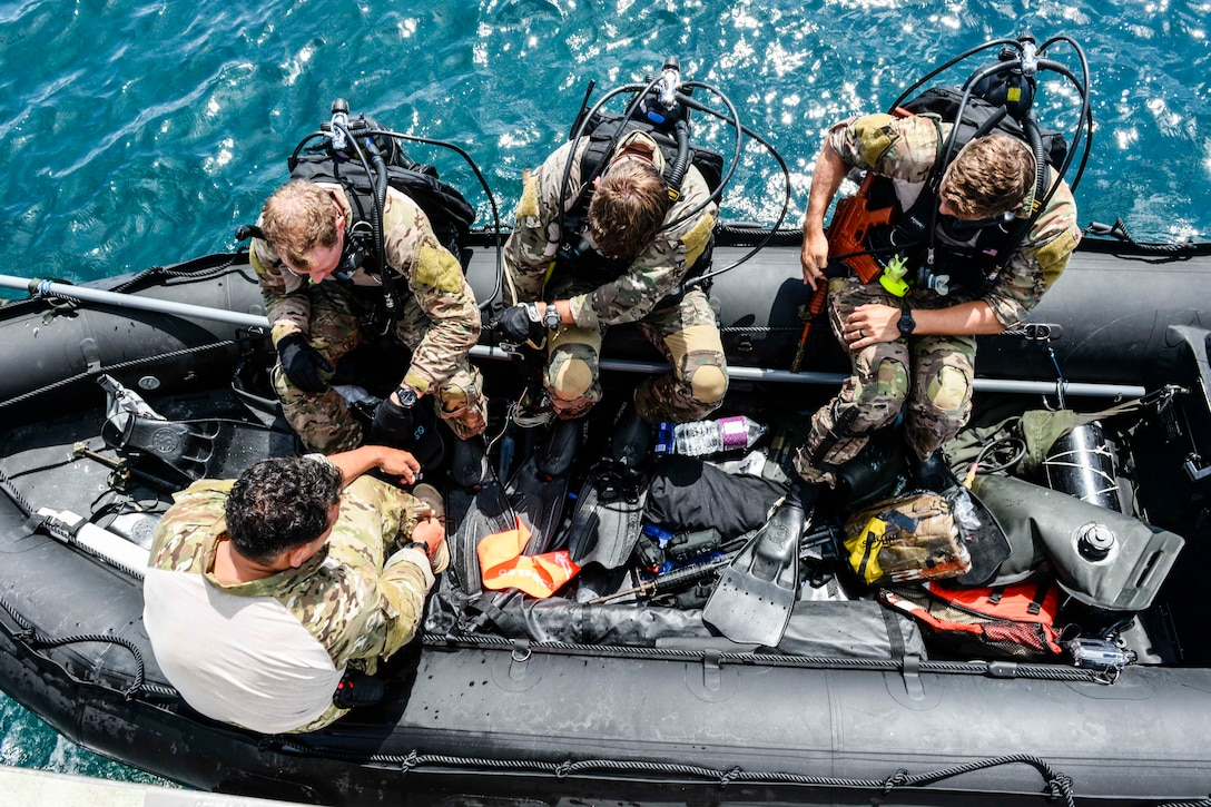 U.S. Air Force Airmen from the 320th Special Tactics Squadron, Kadena Air Base, ready their scuba diving gear during an amphibious operations exercise Sept. 22, 2015, off the west coast of Okinawa, Japan. Teamwork is vital to the successful and safe completion of special tactics objectives, especially in the face of adversities such as harsh weather conditions and terrain. (U.S. Air Force photo by Senior Airman John Linzmeier)