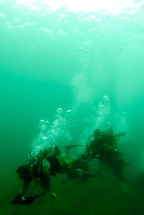 U.S. Air Force combat control Airmen from the 320th Special Tactics Squadron, Kadena Air Base, perform an open-circuit navigation dive during an amphibious operations exercise Sept. 22, 2015, off the West Coast of Okinawa, Japan. Special tactics team Airmen are organized, trained and equipped to conduct special operations core tasks during high-risk combat operations. (Courtesy photo)