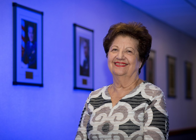 Maria Bandouveres, the executive assistant to the C3I and Networks program executive officer, stands alongside the portraits of all 19 Electronic Systems Division and Electronic Systems Center commanders at Hanscom Air Force Base, Mass., Sept. 15, 2015. Bandouveres, who has been a civil service employee since June 1944, has worked on the command staff for 17 of thoe 19 commanders. (U.S. Air Force photo/Mark Herlihy)