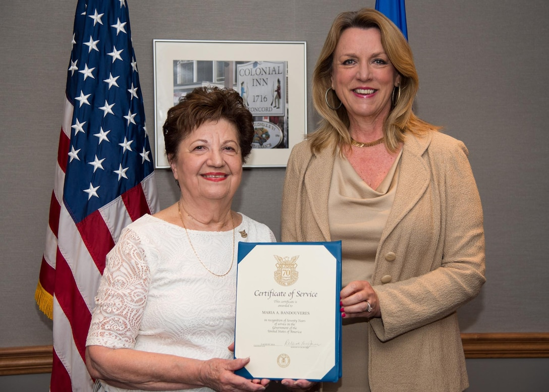 Maria Bandouveres is presented a 70-year federal service pin by Secretary of the Air Force Deborah Lee James during a recognition ceremony in August 2015. Bandouveres has been federally employed at a myriad of organizations since June 1944. She currently serves as the executive assistant to Maj. Gen. Craig S. Olson, the C3I and Networks program executive officer. (U.S. Air Force photo/Mark Herlihy)