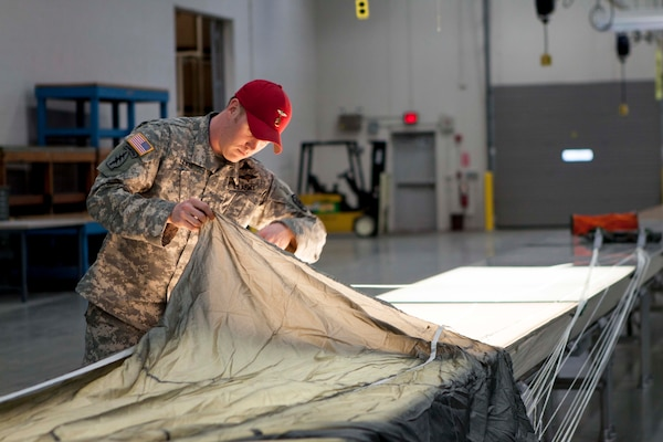 Army Staff Sgt. David Lewis inspects the canopy of a parachute before packing it for use. Lewis is an airborne rigger with DLA Distribution Susquehanna, Pa.