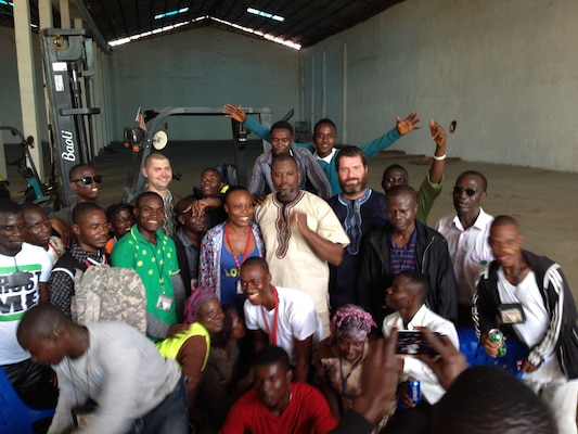 Jason Zeppuhar, second row from back, second from right, pose with other members of the DLA Distribution Expeditionary Team and locals from the area during a party before the team departed Liberia.