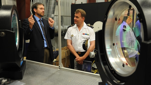 Dr. Chris Lloyd, High Energy Laser Lethality Lead at Naval Surface Warfare Center Dahlgren Division (NSWCDD), briefs French Rear Adm. Christian Dugué, Naval Technical Director for France's Defense Procurement Agency, at the NSWCDD Laser Lethality Lab during the French delegation's NSWCDD visit. Lloyd explained the importance of rigorous modeling and laboratory testing against target materials to ensure high energy laser systems are built that meet the requirements of the warfighter once fielded. NSWCDD is leveraging its knowledge of electromagnetic launchers, hypervelocity projectiles, and directed energy weapons, in addition to its established core capabilities in complex warfare systems development and integration to incorporate electric weapons technology into existing and future fighting forces and platforms.