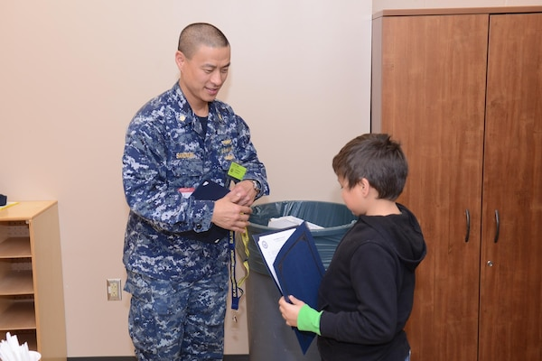 Navy Lt. Cmdr. Brett Sandman, assistant site director of DLA Distribution Norfolk, Va., at New London, Conn., presents a certificate to a Northeast Academy student during the recent Groton ROCKS program.