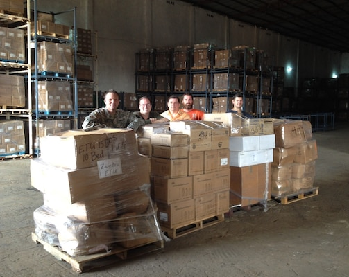 Pete Todd, second from left, and other members of the DLA Distribution Expeditionary Team and a member of DLA Troop Support Medical, pose with supplies in West Africa.