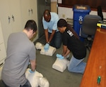 DLA Distribution Corpus Christi, Texas, employees, from top, clockwise, Brian Miller, Samantha Bailey, and Reginald Evans, practice cardiopulmonary resuscitation on mannequins during a class practical exercise.