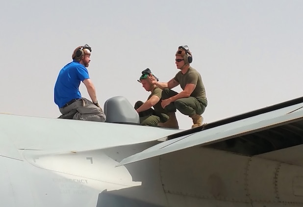 A Marine-contractor team installs the Hatch-Mounted Satellite Communication Antenna System onto the fuselage of a C-130 Hercules aircraft. HMSAS provides secure voice, tactical classified network access, common tactical picture, secure chat and streaming intelligence and reconnaissance video for commanders in the field.