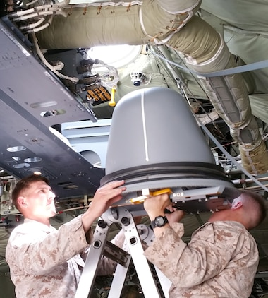 Marines muscle the Hatch-Mounted Satellite Communication Antenna System into the hatch of a C-130 Hercules aircraft. HMSAS provides secure voice, tactical classified network access, common tactical picture, secure chat and streaming intelligence and reconnaissance video for commanders in the field.