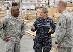 Navy Rear Adm. Valerie K. Huegel, incoming commander to U.S. Central Command's Deployment Distribution Operations Center in Kuwait, tours DLA Distribution Susquehanna, Pa.'s Eastern Distribution Center alongside DLA Distribution commander Army Brig. Gen. Richard Dix, left, and DLA Distribution Susquehanna, Pa., commander Col. Corey New.