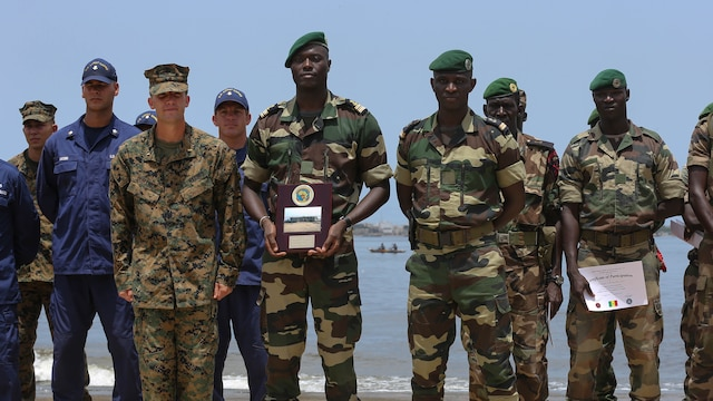 Second Lt. Aaron Burtner, security cooperation team leader, poses for a photo with Compagnie Fusilier de Marin Commandos after completing their final exercise with U.S. service members in Dakar, Senegal, September 17, 2015. The Marines and Coast Guardsmen with Special-Purpose Marine Air-Ground Task Force Crisis Response-Africa spent four weeks training the COFUMACO on basic infantry tactics and small-boat operations as a part of a Maritime Security Force Assistance mission to increase interoperability with Senegal's and strengthen the bond between the partner nations.