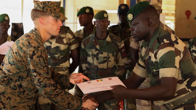 Second Lt. Aaron Burtner, security cooperation team leader, congratulates a Compagnie Fusilier de Marin Commando during his graduation ceremony after completing the final exercise with U.S. service members in Dakar, Senegal, September 17, 2015. The Marines and Coast Guardsmen with Special-Purpose Marine Air-Ground Task Force Crisis Response-Africa spent four weeks training the COFUMACO on basic infantry tactics and small-boat operations as a part of a Maritime Security Force Assistance mission to increase interoperability with Senegal's and strengthen the bond between the partner nations.