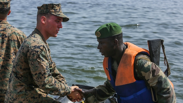 U.S. Marine Lance Cpl. Austin Carpenter, a rifleman, shakes his counterpart Compagnie Fusilier de Marin Commando's hand after successfully completing the final exercise with U.S. service members in Dakar, Senegal, Sept. 17, 2015. The Marines and Coast Guardsmen with Special-Purpose Marine Air-Ground Task Force Crisis Response-Africa spent four weeks training the COFUMACO on basic infantry tactics and small-boat operations as a part of a Maritime Security Force Assistance mission to increase interoperability with Senegal's and strengthen the bond between the partner nations.
