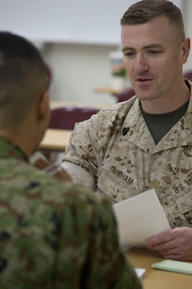Staff Sgt. Robert Durham, operations manager with American Forces Network Iwakuni provides feedback to a Japan Ground Self-Defense Force member during an English seminar at Marine Corps Air Station Iwakuni, Japan, Sept. 14, 2015. Durham showed the translators hand gestures and mannerisms Americans typically used during conversation to help break down possible language barriers between Americans and the Japanese. Seminars like this boost comradery between Americans and Japanese by increasing the ability to communicate with each other.