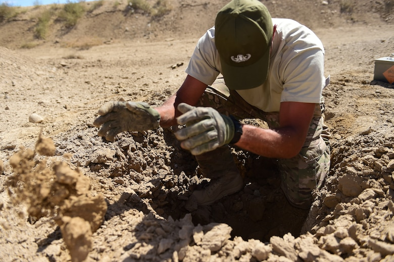 Staff Sgt. Darrel Linkus, 140th Explosive Ordnance Disposal operator, examines the site of a detonation Sept. 23, 2015, at Airburst Range, Colo. Linkus examines the blast site to see if the explosive detonated and produced the results expected. (U.S. Air Force photo by Airman 1st Class Luke W. Nowakowski/Released)