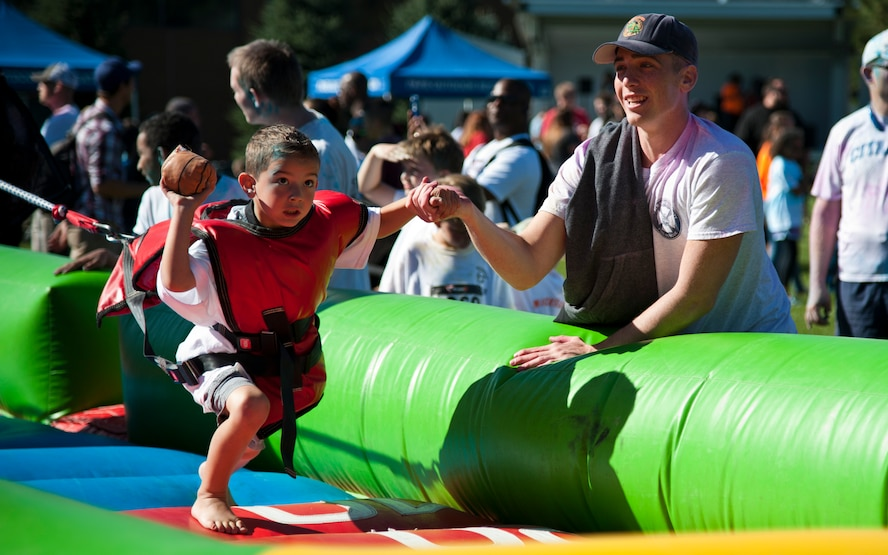 PETERSON AIR FORCE BASE, Colo. – Airman 1st Class Pedro Muina, 21st Civil Engineering Squadron fire department, helps Logan Esplin shoot a miniature basketball during Nickelodeon's Worldwide Day of Play at Patriot Park, Sept. 26, 2015. The annual event encouraged active, healthy lifestyles by providing fun inflatable obstacle courses, games, snacks, a Color Run and demonstrations from the Colorado National Guard, Peterson Fire fighters and Peterson Mobile Emergency Operations Center. (U.S. Air Force photo by Senior Airman Tiffany DeNault)