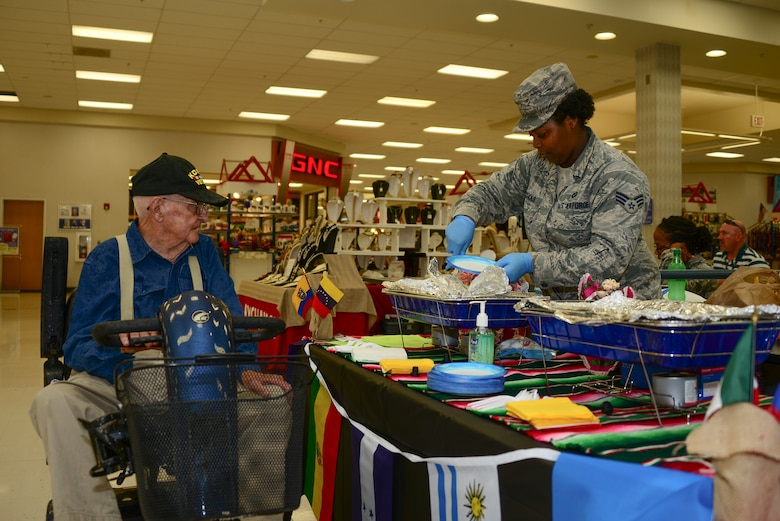 U.S. Air Force Senior Airman El'Thasheia Echols, 355th Operations Support Squadron aviation resource manager, gives food to Noah Tyree, a Korean War veteran at Davis-Monthan Air Force Base, Ariz., Sept. 22, 2015. The food was provided by the Hispanic Heritage Committee free of charge. (U.S. Air Force photo by Airman 1st Class Mya M. Crosby/Released)