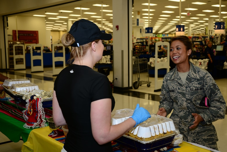 U.S. Air Force Tech. Sgt. Heather Martinez, 355th Fighter Wing Staff NCO in charge of Command Post operations, tells Staff Sgt. Camille Galang, 355th Fighter Wing emergency action controller, what food the Hispanic Heritage Committee provided for the food tasting at Davis-Monthan Air Force Base, Ariz., Sept. 22, 2015. Martinez and other members of the Hispanic Heritage Committee are hosting events to celebrate the heritage of Hispanic Americans. (U.S. Air Force photo by Airman 1st Class Mya M. Crosby/Released)