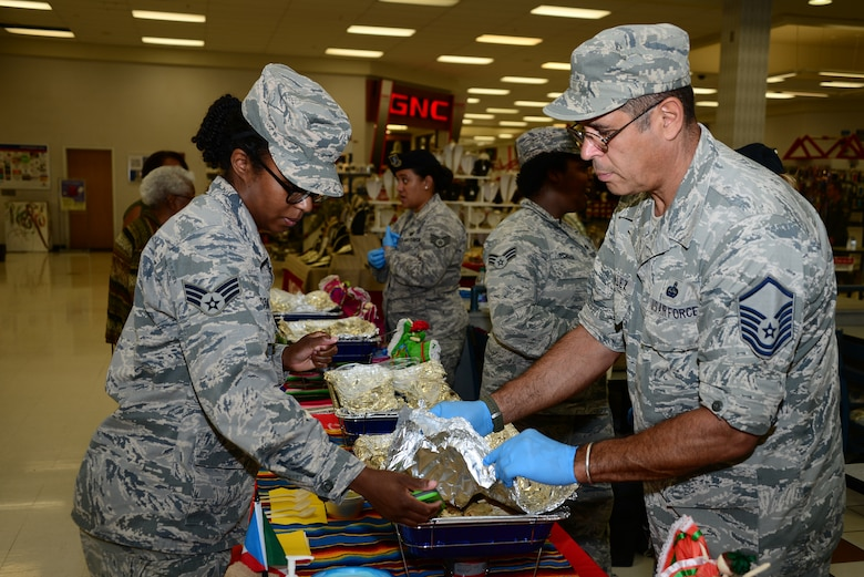 U.S. Air Force Master Sgt. Rafael Gonzalez, 610th Command and Control Squadron quality assurance manager, and Senior Airman Stacey Booker, 355th Aerospace Medicine Squadron public health technician, inspect a food tasting event for Hispanic Heritage Month at Davis-Monthan Air Force Base, Ariz., Sept. 22, 2015. All of the Hispanic food provided for the event was homemade by Desert Lightning Team members. (U.S. Air Force photo by Airman 1st Class Mya M. Crosby/Released)