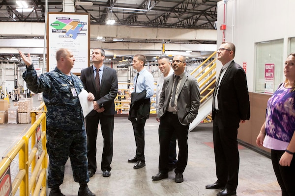 U.S. Navy Lt. Cmdr. David Wright, left, DLA Distribution Susquehanna, explains DLA Distribution Susquehanna's processes at the Consolidation and Containerization Point during the Israeli Navy's visit on July 16.