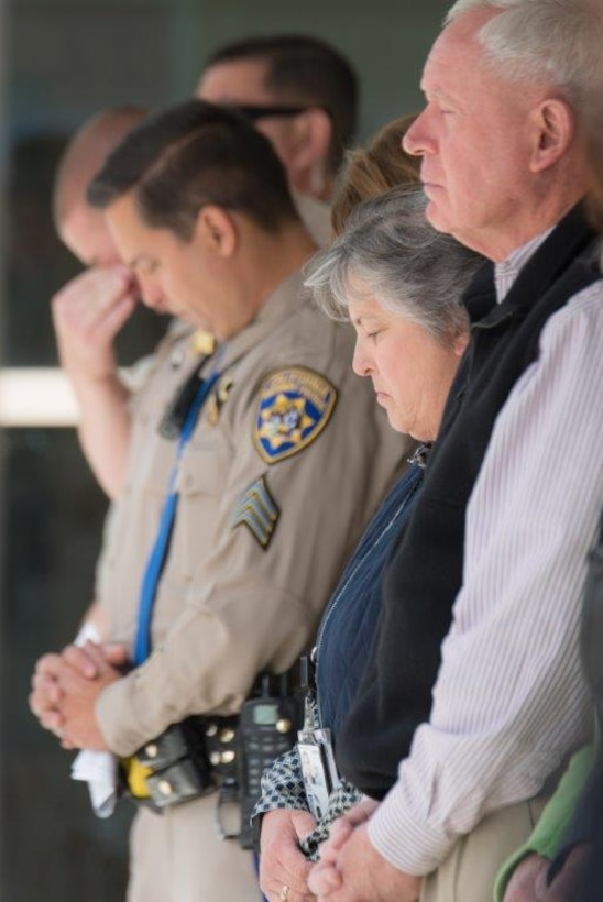 Members of the DLA San Joaquin family and local law enforcement reflect in a moment of silence, paying their respects to the fallen officers.