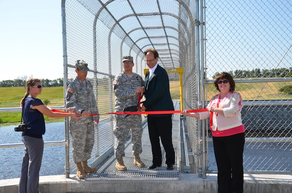 Maj. Gen. John Peabody, Mississippi Valley Division commander, and Todd Sando, North Dakota State Water Commission engineer, dedicate the Tolna Coulee Advance Measures Project with a ribbon cutting ceremony July 19. The 800-foot wide structure is designed to regulate the amount of water that would flow through the coulee.