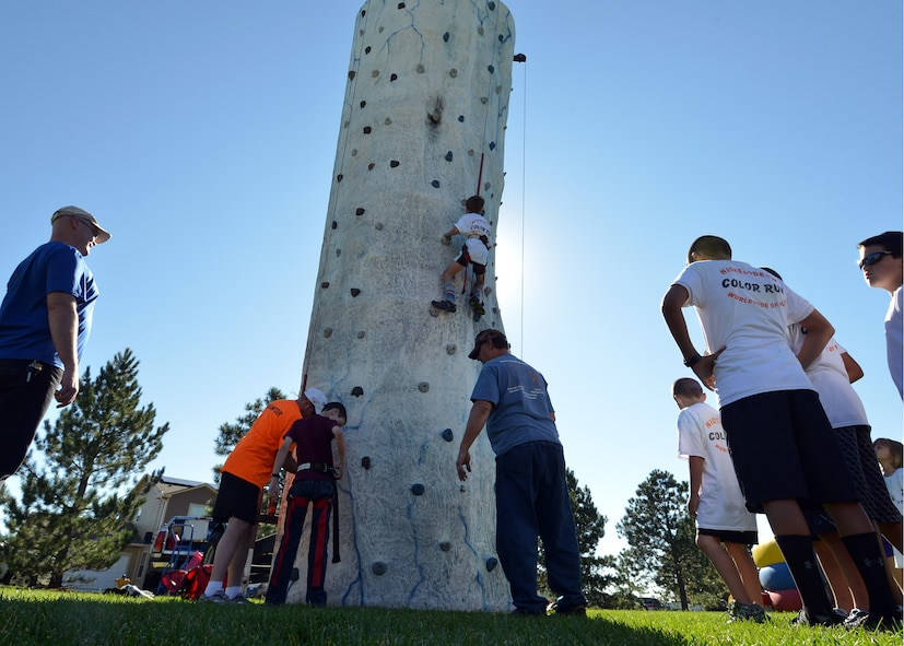 """Children wait for their turn to climb a rock wall during the Worldwide Day of Play event hosted by the Youth Center at Peterson Air Force Base, Colorado, Saturday, Sept. 26, 2015. The event featured a 2k color run, a healthy cooking competition and inflatable obstacle courses but also highlighted National Preparedness Month by featuring activities and booths from the American Red Cross, Ft. Carson's Veterinary Clinic and the Humane Society, the Colorado National Guard, """"Prepare Colorado"""" and the 21st Civil Engineering Squadron Fire Department. (U.S. Air Force photo/Staff Sgt. Debbie Lockhart)"""