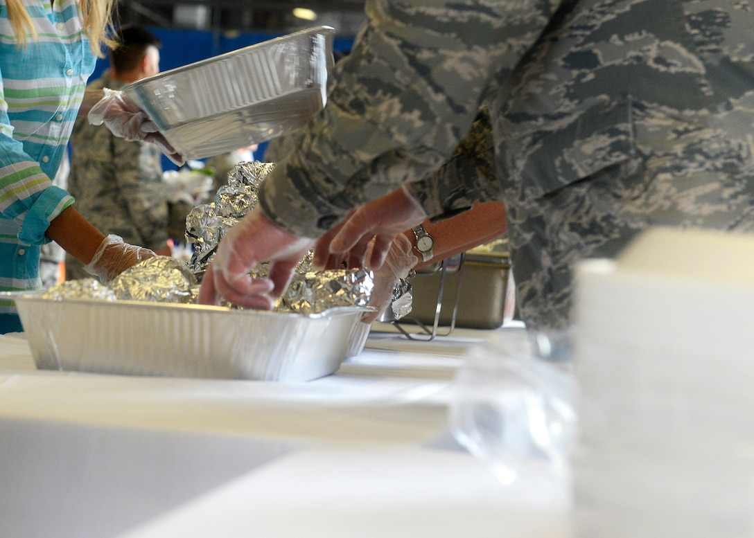 Team Shaw members, along with local volunteers, prepare to hand out food during the 7th Annual Military Appreciation Picnic at Shaw Air Force Base, S.C., Sept. 25, 2015. The event provided Team Shaw Airmen and Soldiers with food such as hamburgers and hot dogs. (U.S. Air Force photo by Airman 1st Class Christopher Maldonado/Released)