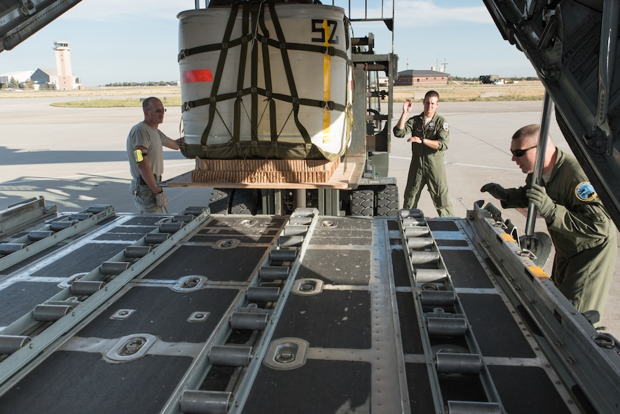 U.S. Air Force loadmasters assigned to the 120th Airlift Wing, Montana Air National Guard work with airmen assigned to the 153rd Logistics Readiness Squadron, Wyoming Air National Guard to load a container delivery system bundle in a C-130H, Sept. 23, 2015, in Cheyenne, Wyoming. The Wyoming Air Guard has been interflying with the Montana Air Guard during their conversion from fighter to cargo aircraft. (U.S. Air National Guard photo by Master Sgt. Charles Delano/Released)