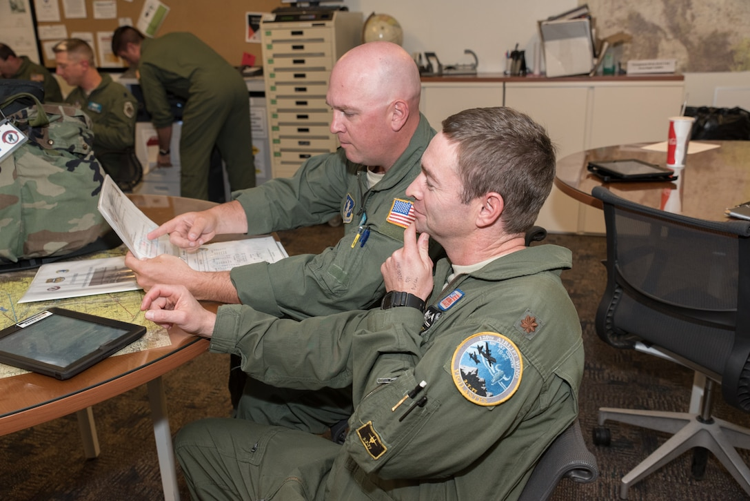 U.S. Air Force Maj. Pat Murphy, 186th Airlift Squadron, Montana Air National Guard, performs flight planning with Maj. Neil Harlow, 187th Airlift Squadron, Wyoming Air National Guard Sept. 23, 2015, in Cheyenne, Wyoming. The two units are collaborating to provide training to the Montana Air National Guard during their conversion from fighter to cargo aircraft. (U.S. Air National Guard photo by Master Sgt. Charles Delano/Released)