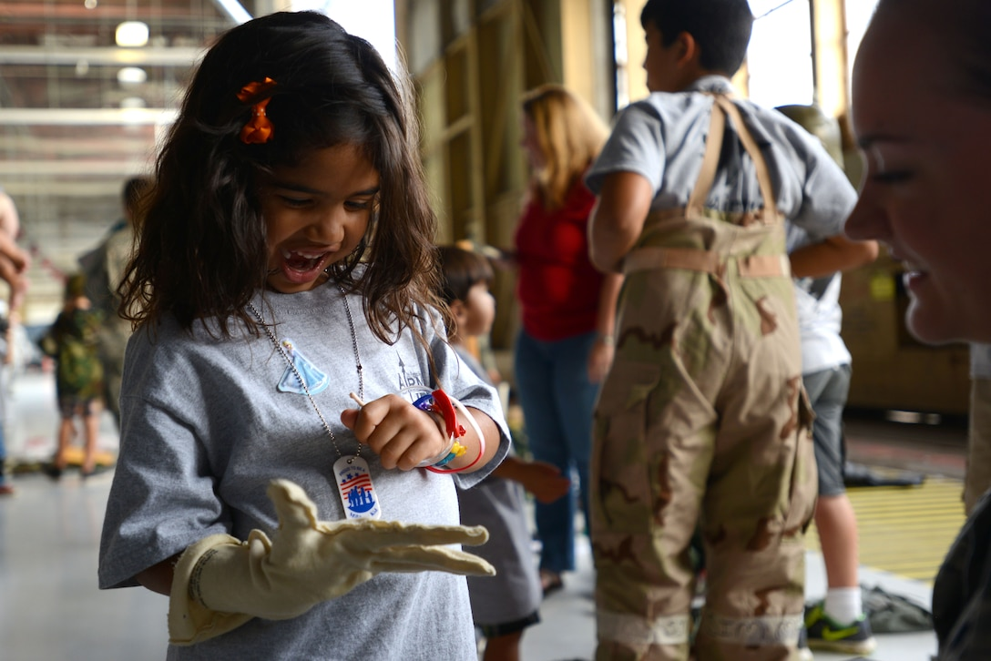 A Team Shaw child wears a glove from a Mission Oriented Protective Posture gear suit during the Kids Meet the Viper event at Shaw Air Force Base, S.C., Sept. 23, 2015. After showing the children how MOPP gear was used, Airmen helped them to try it on for themselves. (U.S. Air Force photo by Airman 1st Class Kelsey Tucker/Released)