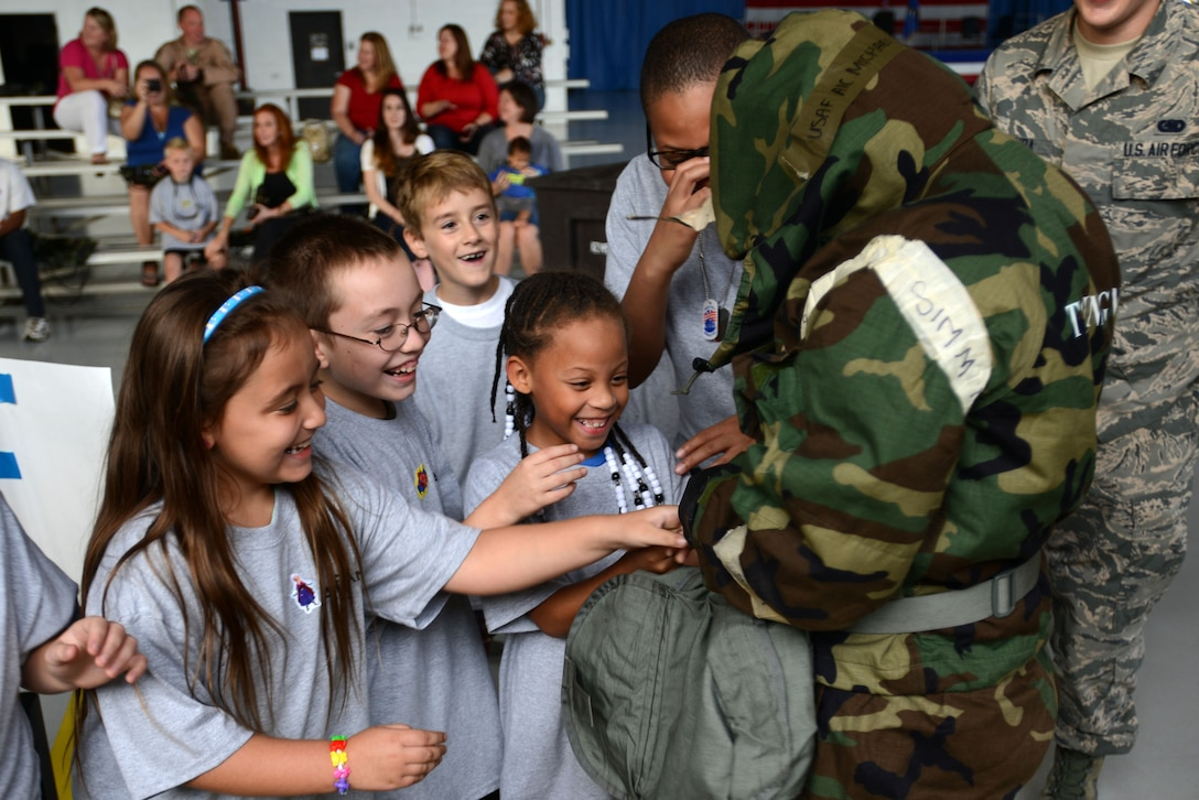 Team Shaw children assist an Airman as she dons her Mission Oriented Protective Posture gear during the Kids Meet the Viper event at Shaw Air Force Base, S.C., Sept. 23, 2015. Two Airmen raced against each other to put on the MOPP gear as the children cheered them on. (U.S. Air Force photo by Airman 1st Class Kelsey Tucker/Released)