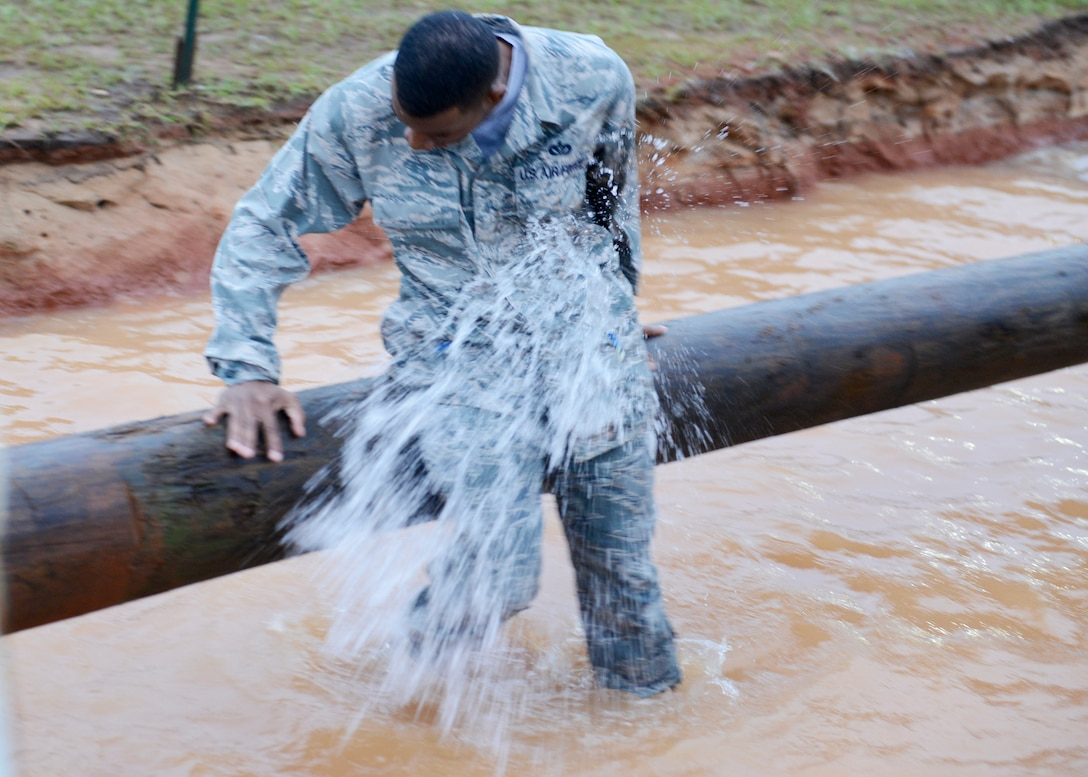 A U.S. Air Force Airman gets hit by a water balloon after falling off a balance log during a 20th Fighter Wing Comprehensive Airman Fitness week obstacle course at Shaw Air Force Base, S.C., Sept. 25, 2015. Airmen volunteers threw the balloons at participants to add further challenges to several of the eight obstacles. (U.S. Air Force photo by Airman 1st Class Christopher Maldonado/Released)