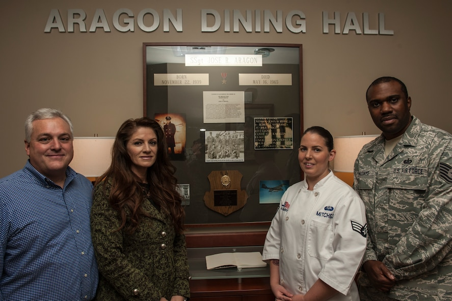 PETERSON AIR FORCE BASE, Colo. – Sandy Aragon Kruse, second from left, poses for a photo with her husband Dominic and two 21st Force Support Squadron Airmen during her visit for a tour of the Aragon Dining Facility, Sept. 25, 2015. Aragon Kruse was visiting the area and toured the facility named after her father for his heroism and sacrifice during the Vietnam War. (U.S. Air Force photo by Airman 1st Class Rose Gudex)