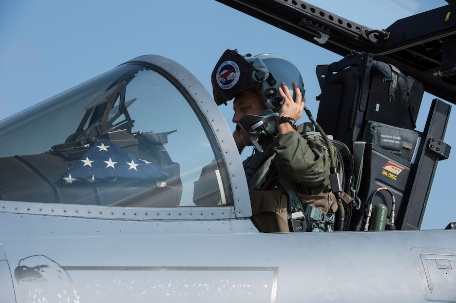 An F-15C Eagle fighter aircraft pilot assigned to the 123rd Expeditionary Fighter Squadron, 142nd Fighter Wing, Oregon Air National Guard, dons his helmet during a theater security package deployment Sept. 25, 2015, at Campia Turzii, Romania. The U.S. Air Force, NATO allies and partners' continuing contributions to develop and improve air readiness are significant in maintaining security and building partnership capacity. (U.S. Air Force photo by Staff Sgt. Christopher Ruano/Released)