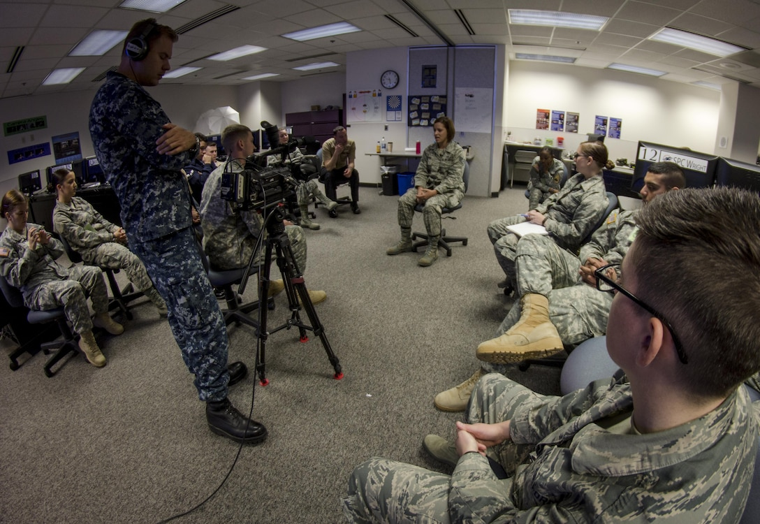 Air Force Staff Sgt. Jaime Ciciora (center), Broadcast Operations and Maintenance Department instructor, teaches Broadcast Communication Specialist Course students techniques for conducting television interviews during video skills training at the Defense Information School, Fort George G. Meade, Md., September 25th, 2015. BCS teaches students to perform skills in video documentation and broadcast journalism. (DoD photo by Tech. Sgt. Nicholas Kurtz/Released)