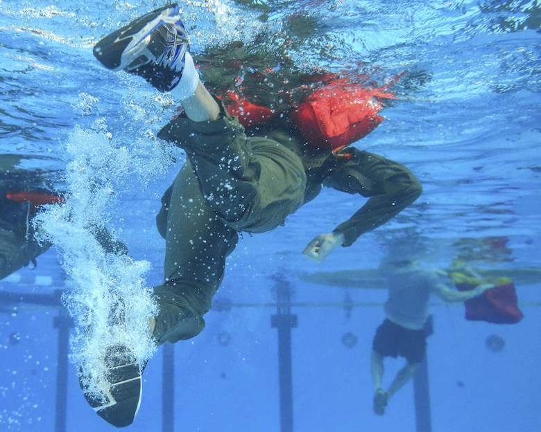 Participants in the survival, evasion, resistance and escape water survival course swim toward a life raft at Yokota Air Base, Japan, Sept. 22, 2015. The water survival course familiarizes students with the equipment and procedures used in the event of an aircraft emergency. (U.S. Air Force photo/Airman 1st Class Elizabeth Baker)