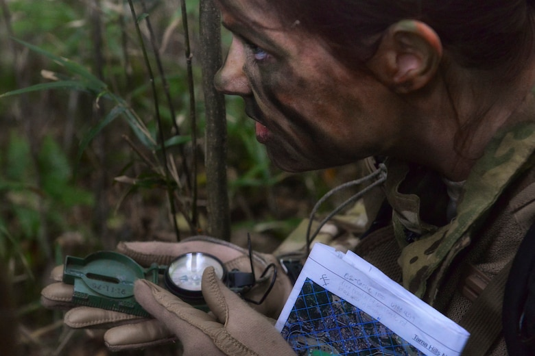 Capt. Allison Ohlinger, a 36th Airlift Squadron instructor navigator, uses a compass to navigate for her team during a survival, evasion, resistance and escape combat survival course at Tama Hills Recreation Area, Japan, Sept. 24, 2015. SERE uses realistic wilderness situations to teach students the importance, difficulty and technique of navigation using simple instruments. (U.S. Air Force photo/Airman 1st Class Elizabeth Baker)