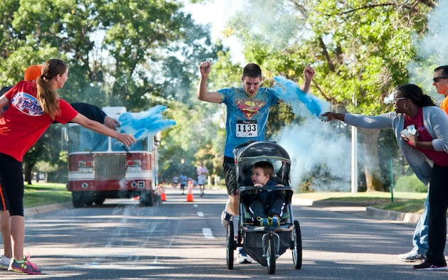 First Lt. Nathan Flack, the 21st Communications Squadron flight commander, and his son, Titus, finish the Color Run during Nickelodeon's Worldwide Day of Play at Patriot Park on Peterson Air Force Base, Colo., Sept. 26, 2015. The event included a healthy cooking challenge, inflatable obstacle courses, climbing wall, games, snacks and demonstrations from the Peterson Fire Station and Mobile Emergency Operations Center. (U.S. Air Force photo/Senior Airman Tiffany DeNault)