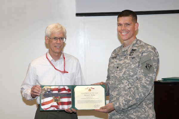 Steve Rothe (left), Omaha District Project Manager, receives the Superior Civilian Service Award from Omaha District Commander Colonel John Henderson (right) upon his retirement after nearly 40 years of public service.