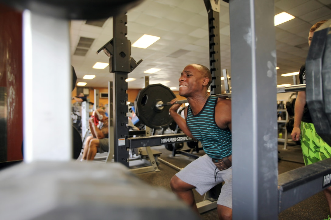 Cpl. Ajunelle Simmons performs a weighted squat at Marine Corps Air Station Cherry Point, Sept. 27, 2015.  The Hancock gym and Devil Dog gym's hours will increase by more than 40 hours per week beginning Oct. 1, 2015, collectively between the two fitness facilities. The change in hours comes from the concerns of Marines on the air station being heard by their senior leadership. Simmons is a food service specialist with Marine Wing Support Squadron 274. (U.S. Marine Corps photo by Lance Cpl. Jason Jimenez/Released)