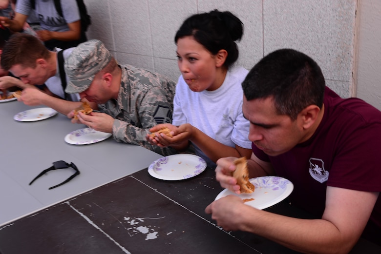 Contestants eat pumpkin pie in the first round of the pie eating contest starting the Osan Cup Sept. 29, 2015, at Osan Air Base, Republic of Korea. The Osan Cup  readiness, teamwork and fun, while building relationships across Team Osan readiness, teamwork and fun, while building relationships across Team Osan had many activities designed to strengthen readiness and teamwork while having fun. (U.S. Air Force photo by Staff Sgt. Benjamin Sutton)