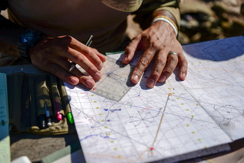 British Army Sgt. Daniel Campbell, Royal Lancers joint tactical air controller, uses a protractor, map and navigation skills to plan preemptive targets at Barry M. Goldwater Range, Ariz., Sept. 23, 2015. The British Armed Forces JTACs are the link between air and ground communications and are charged with ensuring that they can direct any ordnance that leaves an aircraft while protecting civilians and friendly troops at all times. (U.S. Air Force photo by Airman 1st Class Chris Drzazgowski/Released)