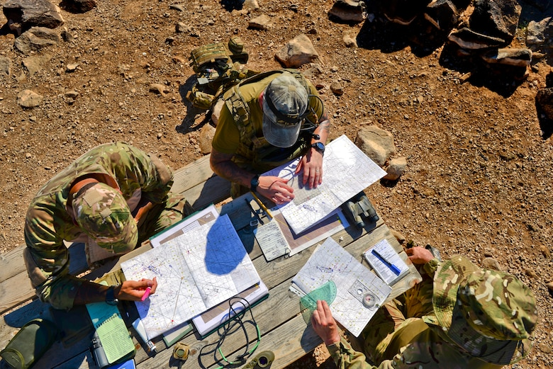 British Armed Forces joint tactical air controllers administer navigation skills using trigonometry and maps at Barry M. Goldwater Range, Ariz., Sept. 23, 2015. The JTACs utilized BMGR because of its abundance of air traffic which provides more opportunities to practice tactical air control. (U.S. Air Force photo by Airman 1st Class Chris Drzazgowski/Released)
