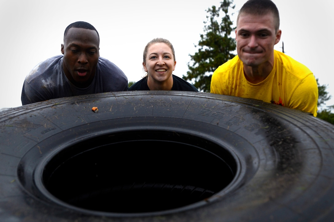 U.S. Air Force Airmen flip a tire during a 20th Fighter Wing Comprehensive Airman Fitness week obstacle course at Shaw Air Force Base, S.C., Sept. 25, 2015. After flipping the tire, Airmen had to accomplish three additional obstacles to complete to course. (U.S. Air Force photo by Senior Airman Jensen Stidham/Released)