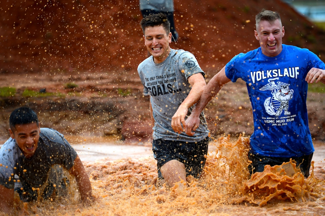 U.S. Air Force Airmen run through a mud pit during a 20th Fighter Wing Comprehensive Airman Fitness week obstacle course at Shaw Air Force Base, S.C., Sept. 25, 2015. Airmen were challenged throughout the event by a series of eight obstacles meant to test the physical domain of CAF. (U.S. Air Force photo by Senior Airman Jensen Stidham/Released)
