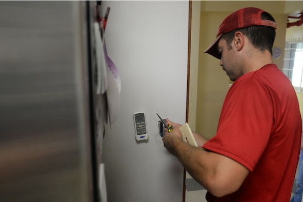 Staff Sgt. Scott Brown, 554th RED HORSE electrical contingency instructor, replaces a light switch Sept. 26, 2015, at the Guma San Jose Homeless Shelter, Dededo, Guam.  The Airmen offered their specialized services to assist with the shelter's electrical, plumbing and air conditioning issues. (U.S. Air Force photo by Senior Airman Joshua Smoot/Released)