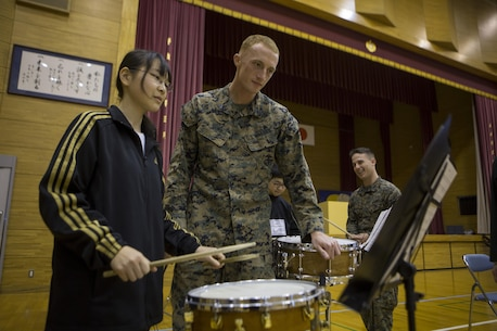 U.S. Marine Sgt. James D. Lowe helps a Shichijo Junior High School band drummer March 6, in the school's gymnasium in Kumamoto, Japan. The Western Army Band and III MEF Band will perform with and coach the students during their visit.Lowe is a drummer with the III Marine Expiditionary Force Band. (U.S. Marine Corps photo by Cpl. Tyler Ngiraswei/ Released)