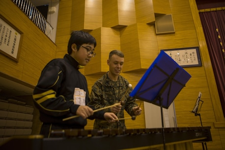 U.S. Marine Cpl. Ryan O. Vangosen instructs a student at Shichijo Junior High School, Kumamoto, Japan, Mar. 6. The Japan Ground Self-Defense Force Western Army Band and III Marine Expeditionary Force Band will perform with and  coach the students during their visit.The Marines were in Kumamoto to participate in the Western Army Band Music Festival, which celebrates the 60th Anniversary of the Western Army Band. (U.S. Marine Corps photo by Cpl. Tyler Ngiraswei/ Released)