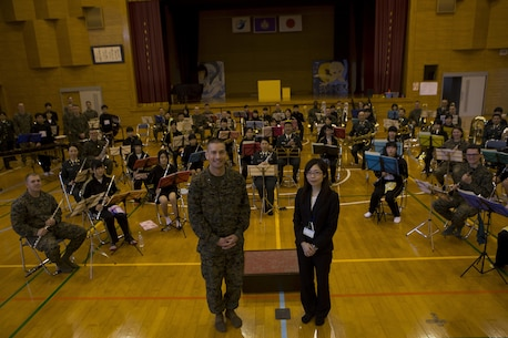 The III Marine Expeditionary Force Band, Japan Ground Self-Defense Force Western Army Band and Shichijo Junior High School Band pose for a photo Mar. 6, in the gymnasium at Shichijo Junior High School, Kumamoto, Japan. The Western Army Band and III MEF Band performed with and  coached the students during their visit.The Marines were in Kumamoto to participate in the Western Army Band Music Festival, which celebrates the 60th Anniversary of the Western Army Band.