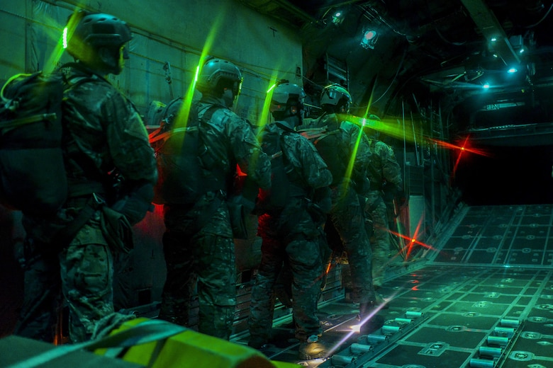 Survival, evasion, resistance and escape specialists wait before performing static line jumps as the door of a C-130 Hercules, assigned to Dobbins Air Reserve Base, Ga., opens over the Nevada Test and Training Range, Nev., March 11, 2016. SERE specialists lead the Air Force emergency parachuting program and conduct extensive testing of parachuting systems. They are uniquely suited to analyze the operating environment to plan for evasion, captivity and recovery considerations. (U.S. Air Force photo/Airman 1st Class Kevin Tanenbaum)